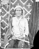 view Portrait (Front) of Native Doctor, Man, in Partial Native Dress with Ornaments and Holding Quirt?; Rifle and Blankets in Background MAY 1903 digital asset number 1