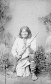 view Portrait (Front) of Goyathlay (One Who Yawns), Called Geronimo, Medicine Man, Prophet and Leader, in Partial Native Dress and Holding Rifle 1886 digital asset number 1