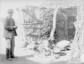 view Woman Making Clay Pot Near Mud and Pole House; Manos, Metates, Baskets, and Man Nearby 1894 digital asset number 1