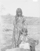 view Woman and Child, Both in Native Dress with Ornaments, Child Reading Book 1900 digital asset number 1