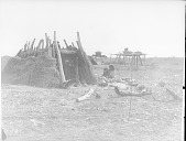 view Mother and Child Near Pole and Brush House; Melons, Cooking Pots and Storage Platforms Nearby 1900 digital asset number 1