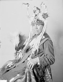 view Portrait (Profile) of William Charlie, Interpreter, in Native Dress with Headdress and Ornaments and Holding Two Fans APR 1905 digital asset number 1