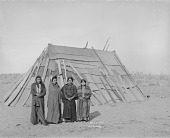 view Two Men and Two Women, All in Native Dress with Ornaments, Near Woven Mat and Wood House 1900 digital asset number 1