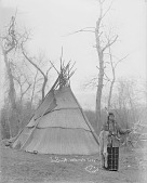view Joe Benett in Native Dress with Ornaments and Bear Claw Headband and Holding Pipe-tomahawk and Knife; Woven Mat Tipi Nearby 1900 digital asset number 1