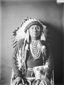 view Portrait (Front) of Hinmaton-Yalatkit or Hin-Ma-Toe-Ya-Lut-Kiht (Thunder Coming From The Water Up Over The Land), Called Chief Joseph, in Native Dress with Headdress and Ornaments and Holding Bag FEB 1903 digital asset number 1