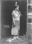 view Tirzah Trask in Native Dress with Ornaments and Holding Bag, Other Bag Nearby 1900 digital asset number 1