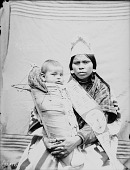 view Portrait of Kupt in Partial Native Dress with Woven Hat and Ornaments and Holding Child in Cradleboard 1900 digital asset number 1