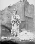 view Princess Eagle Feather in Native Dress with Ornaments and Holding Bag; Other Bags, Blankets, and Cloth Covered House Nearby 1900 digital asset number 1
