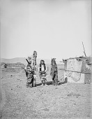 view Three Men, All in Partial Native Dress with Ornaments, Two with Headdresses, One Holding Staff, Cloth Covered House Nearby 1900 digital asset number 1