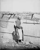 view Man in Partial Native Dress and Carrying Quiver, Near Woven Mat Covered House 1900 digital asset number 1