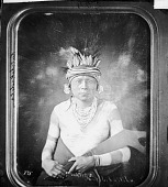 view Portrait (Front) of Bum-Be-Sun or Kutchekaitika in Native Dress with Body Paint, Headdress, and Ornaments and Holding War Club? 1869 digital asset number 1