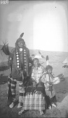 view Mato Hitunkasan [Weasel Bear] with his Wife and Child Partial Native Dress with Ornaments, One with Breastplate; Tipis in Background 1892 digital asset number 1