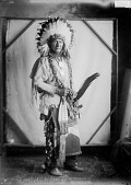 view Portrait (Front) of Chief Hogan-Luta (Red Fish) in Native Dress with Headdress and Two Peace Medals and Holding Fan, Bag and Pipe 1912 digital asset number 1