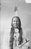 view Portrait (Front) of Tatanka Wanaghi or Tatanka Wanagi or Tatanka Wanaxi or Tah-Tun-Ka-We-Nah-Hi (Buffalo Bulls Ghost) or (Bulls Ghost) in Partial Native Dress with Andrew Johnson and Martin Van Buren Peace Medals and Holding Pipe 1884 digital asset number 1