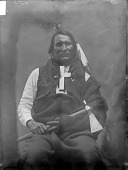 view Portrait (Front) of Man in Partial Native Dress with Cross Necklace and Holding Pipe-tomahawk n.d digital asset number 1