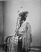 view Profile of Ta-Tan-Ka-Han-Ska (Long Fox or Long Buffal O Bull) in wearing feathered skunk hat and holding pipe and beaded and quilled bag digital asset: Profile of Ta-Tan-Ka-Han-Ska (Long Fox or Long Buffal O Bull) in wearing feathered skunk hat and holding pipe and beaded and quilled bag