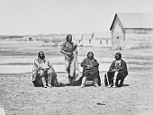 view Lone Horn; Pipe; Grass; and Young Elk standing and seated near wood frame buildings at Fort Laramie digital asset: Lone Horn; Pipe; Grass; and Young Elk standing and seated near wood frame buildings at Fort Laramie