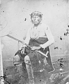 view Portrait (Front) of Non-Pe-Wa-The or No-Pa-Wal-La (Fear Inspiring), Called Savage, in Partial Native Dress with Headdress and Ornaments 1868 digital asset number 1