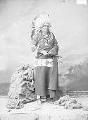 view Portrait (Front) of Chief Ta-Ton-Ga-Non-Zhin or Ta-Tan-Ka-Nu-Zhe (Standing Buffalo Bull) in Partial Native Dress with Headdress and Bear Claw Necklace and Holding Pipe-tomahawk 14 NOV 1877 digital asset number 1