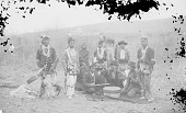view Group of Eleven Grass Dancers in Partial Dance Costume, Three with Drumsticks Around Drum; Pakalapzkt's Wood Frame House in Background 1887 digital asset number 1