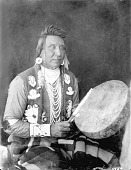 view Bear Ground, Outstanding Singer, in Partial Native Dress with Ornaments and Playing Drum n.d digital asset number 1