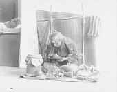 view Portrait of Man in Native Dress Writing On Birchbark; Drums, Rattle, Drumsticks, Woven Bags?, and Woven Mats Nearby n.d digital asset number 1