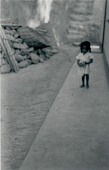view [Adopted daugher of Manoel, chief drummer at Gantois, holding pot and walking in alley in front of Manoel's house], circa 1938 digital asset number 1