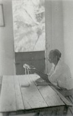 view [Filenha sitting at table in Sabina's home, making lace on frame], 1938 October digital asset number 1