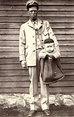 view Photograph of letter carrier with child in mailbag digital asset number 1
