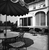view [Unidentified Garden in Unknown Location]: terrace and furniture, with screened porch in background. digital asset: [Unidentified Garden in Unknown Location] [contact print]: terrace and furniture, with screened porch in background.