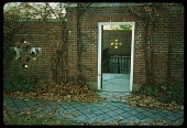 view [Hyland-Schutz Garden]: facing south from driveway; street side, laundry gate with pierced brick wall. digital asset: [Hyland-Schutz Garden]: facing south from driveway; street side, laundry gate with pierced brick wall.: 1987.