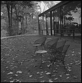 view [Glass House]: lawn furniture provides seating outside of the Glass House. digital asset: [Glass House] [safety film negative]: lawn furniture provides seating outside of the Glass House.