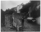 """view [Miscellaneous Sites in Clovelly, Devon, England]: a man on the cobblestone street leading to the harbor, with a boat on the right whose inscription reads """"Lydia Clovelly James Cruse."""" digital asset: [Miscellaneous Sites in Clovelly, Devon, England] [glass negative]: a man on the cobblestone street leading to the harbor, with a boat on the right whose inscription reads """"Lydia Clovelly James Cruse."""""""