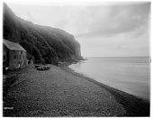 view [Miscellaneous Sites in Clovelly, Devon, England]: stone building and boats on the shore in the harbor area. digital asset: [Miscellaneous Sites in Clovelly, Devon, England] [glass negative]: stone building and boats on the shore in the harbor area.