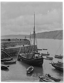 view [Miscellaneous Sites in Clovelly, Devon, England]: fishing boats and rowboats in the harbor at high tide. digital asset: [Miscellaneous Sites in Clovelly, Devon, England] [glass negative]: fishing boats and rowboats in the harbor at high tide.