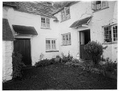 view [Miscellaneous Sites in Clovelly, Devon, England]: a house with decorative plants around its entrance. digital asset: [Miscellaneous Sites in Clovelly, Devon, England] [glass negative]: a house with decorative plants around its entrance.