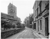 view [Miscellaneous Sites in Bowness-on-Windermere, Cumbria, England]: looking along Church Street, with St. Martin's Church and churchyard on the left. digital asset: [Miscellaneous Sites in Bowness-on-Windermere, Cumbria, England] [glass negative]: looking along Church Street, with St. Martin's Church and churchyard on the left.