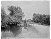 view [Miscellaneous Sites in Sussex, England, Series 1]: an unidentified location with a bridge leading toward a village or town. digital asset: [Miscellaneous Sites in Sussex, England, Series 1] [glass negative]: an unidentified location with a bridge leading toward a village or town.
