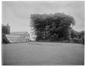 view [Clovelly Court]: tennis court and end of the conservatory/orangerie/greenhouse at the Clovelly Court country house. digital asset: [Clovelly Court] [glass negative]: tennis court and end of the conservatory/orangerie/greenhouse at the Clovelly Court country house.