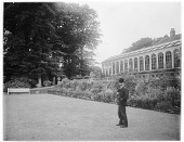 view [Clovelly Court]: an unidentified man standing in front of the conservatory/orangerie/greenhouse at the Clovelly Court country house. digital asset: [Clovelly Court] [glass negative]: an unidentified man standing in front of the conservatory/orangerie/greenhouse at the Clovelly Court country house.