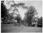 view [Clovelly Court]: entrance gate and gatehouse for Clovelly Court, seen from outside the property. digital asset: [Clovelly Court] [glass negative]: entrance gate and gatehouse for Clovelly Court, seen from outside the property.