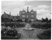 view [Gravetye Manor]: looking along a garden walkway toward a sundial with the house beyond. digital asset: [Gravetye Manor] [glass negative]: looking along a garden walkway toward a sundial with the house beyond.