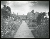 view [Gravetye Manor]: looking from one of the gardens toward the house. digital asset: [Gravetye Manor] [lantern slide]: looking from one of the gardens toward the house.
