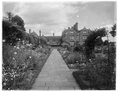 view [Gravetye Manor]: looking along a garden walkway toward the house. digital asset: [Gravetye Manor] [glass negative]: looking along a garden walkway toward the house.