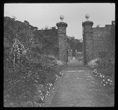 view [Unidentified Location]: a brick wall, gate, and garden borders in an unidentified location, probably at Esher Place, Surrey. digital asset: [Unidentified Location] [lantern slide]: a brick wall, gate, and garden borders in an unidentified location, probably at Esher Place, Surrey.