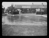 view [Court Farm]: a large pool, possibly a swimming pool, with a central aerating fountain. digital asset: [Court Farm] [lantern slide]: a large pool, possibly a swimming pool, with a central aerating fountain.