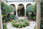 view [La Salona]: Two story open colonnaded courtyard with tile fountains surrounded by potted begonias, ferns, and ficus. digital asset: [La Salona]: Two story open colonnaded courtyard with tile fountains surrounded by potted begonias, ferns, and ficus. : 2017 March 2