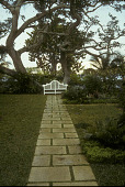 view [Lake House]: stone walkway leads to white settee and Gumbo Limbo trees; water and hotels in distant background digital asset: [Lake House]: stone walkway leads to white settee and Gumbo Limbo trees; water and hotels in distant background: 1993 Apr.