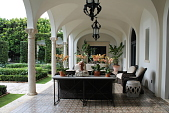 view [The Charles Residence]: Coral columns support a groin vaulted ceiling and open to the parterre. Multiple pots of orchids (Phalaenopsis spp.), wicker furniture, and there are two pots of Heliconia psillacorum by a doorway at the far end. digital asset: [The Charles Residence]: Coral columns support a groin vaulted ceiling and open to the parterre. Multiple pots of orchids (Phalaenopsis spp.), wicker furniture, and there are two pots of Heliconia psillacorum by a doorway at the far end.