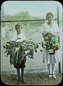 view [School Garden Exhibitions]: a boy and a girl each holding a basket of arranged vegetables and a basket of arranged flowers. digital asset: [School Garden Exhibitions]: a boy and a girl each holding a basket of arranged vegetables and a basket of arranged flowers.: [between 1914 and 1949?]
